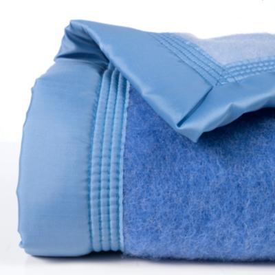Pure laine vierge Woolmark de qualité supérieure, 600 g/m², foulée, lavée et dégraissée à fond. Traitée anti-mites. Finition ruban de satin 100 % polyamide, maintenu par 4 piqûres renforcées par un point d'arrêt à chaque angle pour plus de solidité. Netto