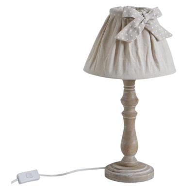 Harmonie de bois, de métal et de coton, la lampe en bois reflète une conceptualisation tournée vers le romantisme et la sensualité. Elle est munie d'un piétement sculpté attirant les regards sur un abat-jour plissé. Un ruban à pois et décliné en un noeud